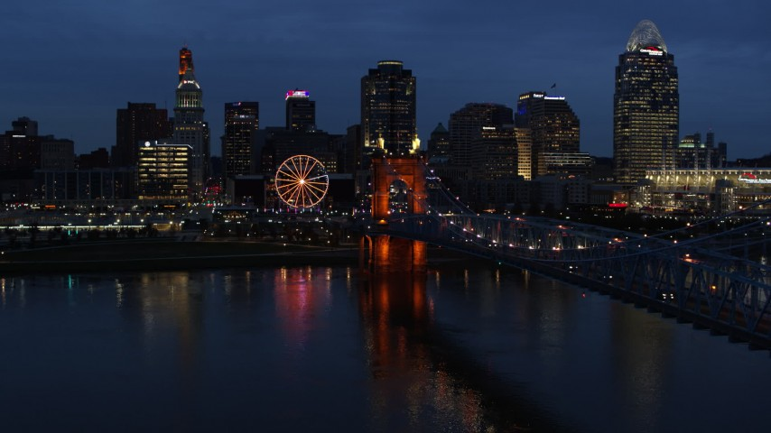 5.7K aerial video of lights of city skyline and bridge at twilight while descending by river, Downtown Cincinnati, Ohio Aerial Stock Footage | DX0001_003180