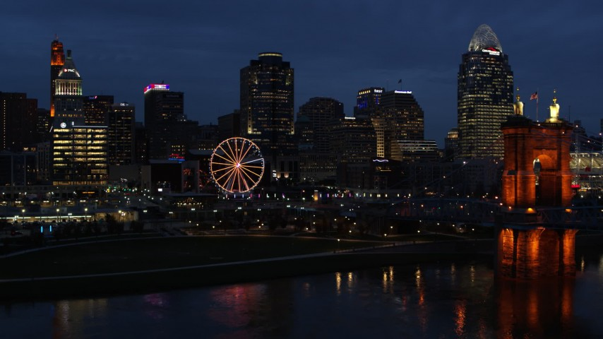 5.7K stock footage aerial video fly away from skyscraper and Ferris wheel at twilight, reveal the river and bridge, Downtown Cincinnati, Ohio Aerial Stock Footage | DX0001_003183