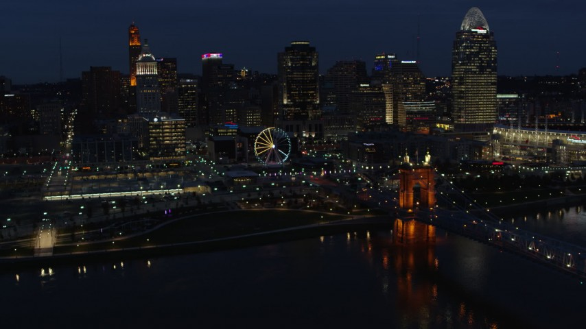 5.7K stock footage aerial video flying by the city skyline at twilight, seen from river near bridge, Downtown Cincinnati, Ohio Aerial Stock Footage | DX0001_003187