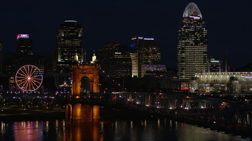 5.7K stock footage aerial video fly over Roebling Bridge at night to approach city skyline, Downtown Cincinnati, Ohio Aerial Stock Footage DX0001_003191
