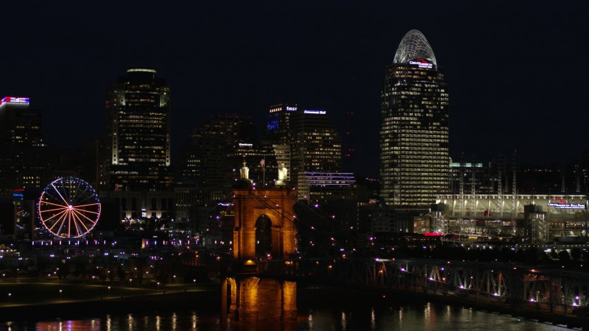 5.7K aerial video descend and pass bridge, tall skyscrapers and Ferris wheel at night in Downtown Cincinnati, Ohio Aerial Stock Footage | DX0001_003194
