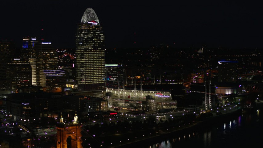 5.7K aerial video of a tall skyscraper and the baseball stadium at night in Downtown Cincinnati, Ohio Aerial Stock Footage | DX0001_003195