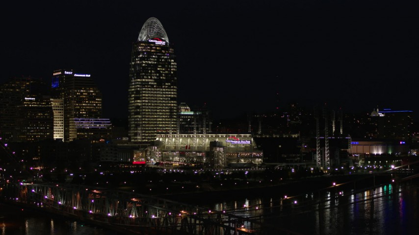 5.7K aerial video descend by tall skyscraper and the baseball stadium at night, reveal bridge, Downtown Cincinnati, Ohio Aerial Stock Footage | DX0001_003196