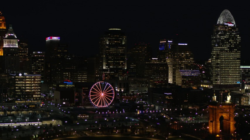 5.7K aerial video ascend with a view of the city skyline and Ferris wheel at night, Downtown Cincinnati, Ohio Aerial Stock Footage | DX0001_003197