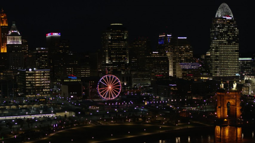 5.7K stock footage aerial video flying by the city skyline and Ferris wheel at night near Roebling Bridge, Downtown Cincinnati, Ohio Aerial Stock Footage | DX0001_003198