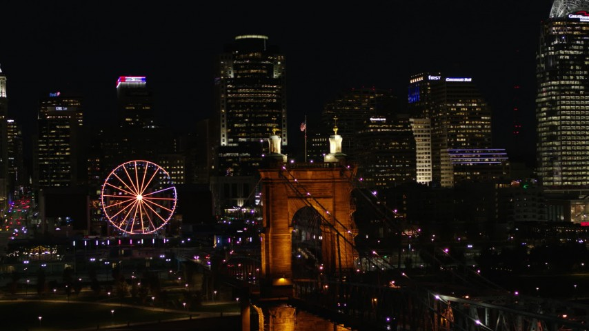 5.7K aerial video close orbit of Roebling Bridge at night, reveal city skyline in background, Downtown Cincinnati, Ohio Aerial Stock Footage | DX0001_003200