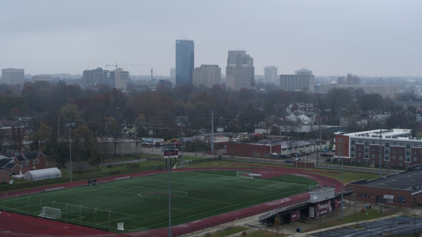 5.7K aerial video of the city skyline seen while descending by football field, Downtown Lexington, Kentucky Aerial Stock Footage | DX0001_003209
