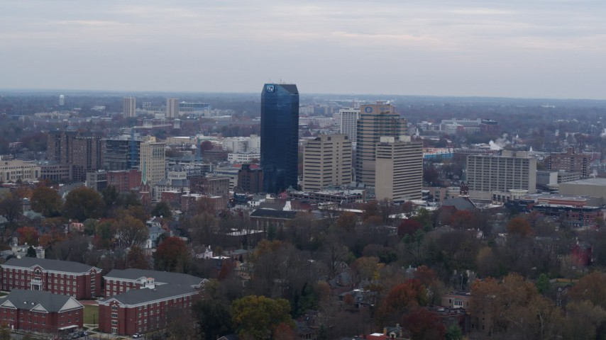 5.7K stock footage aerial video slowly passing the city's skyline, seen from tree-lined neighborhoods, Downtown Lexington, Kentucky Aerial Stock Footage | DX0001_003213