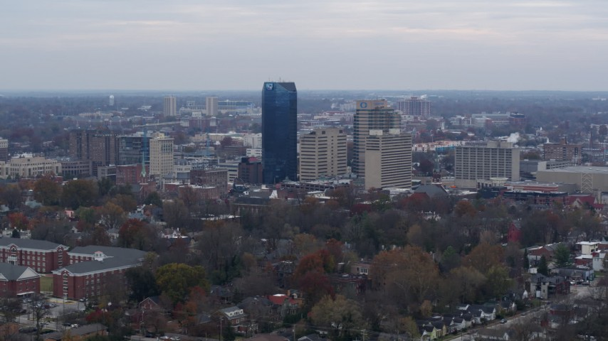 5.7K stock footage aerial video focus on the city's skyline from tree-lined neighborhoods, Downtown Lexington, Kentucky Aerial Stock Footage | DX0001_003214