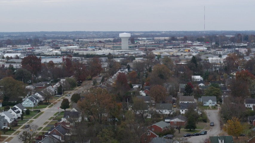 5.7K stock footage aerial video descend toward homes with view of a water tower surrounded by warehouses in Lexington, Kentucky Aerial Stock Footage | DX0001_003238