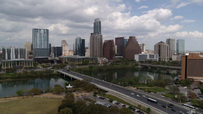 5.7K aerial video of the city's skyline while flying by First Street Bridge and Lady Bird Lake, Downtown Austin, Texas Aerial Stock Footage | DX0002_102_001