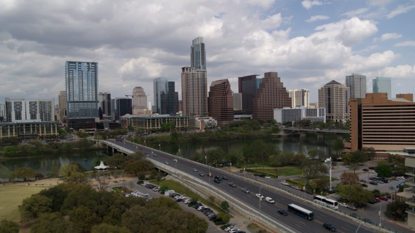 5.7K aerial video the city's skyline while passing First Street Bridge and Lady Bird Lake, Downtown Austin, Texas Aerial Stock Footage | DX0002_102_002