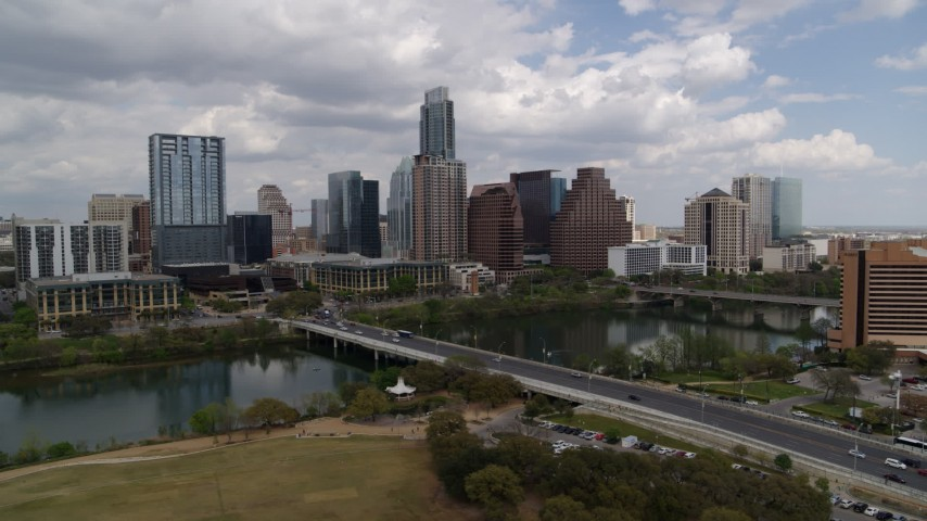 5.7K stock footage aerial video slowly pass First Street Bridge and Lady Bird Lake with view of skyline, Downtown Austin, Texas Aerial Stock Footage | DX0002_102_004