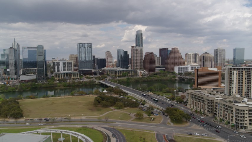 5.7K aerial video of a reverse view of First Street Bridge, Lady Bird Lake and the city skyline, Downtown Austin, Texas Aerial Stock Footage | DX0002_102_009