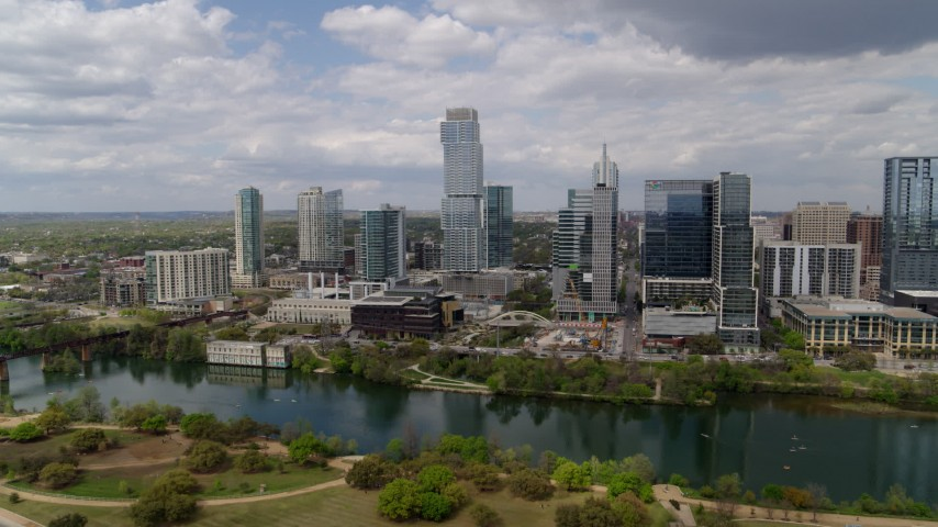 5.7K aerial video of a reverse view of city skyscrapers across Lady Bird Lake, Downtown Austin, Texas Aerial Stock Footage | DX0002_102_013