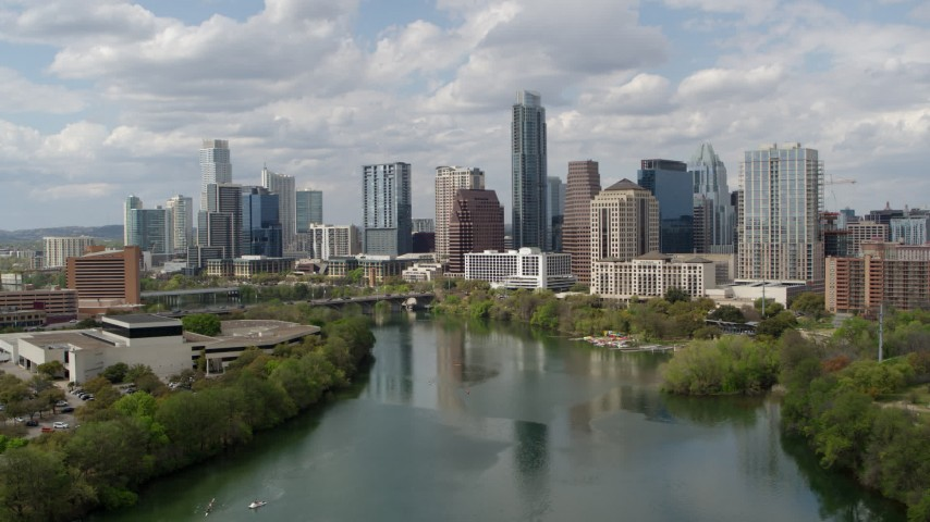 5.7K aerial video of a reverse view of the city skyline while flying over Lady Bird Lake, Downtown Austin, Texas Aerial Stock Footage | DX0002_102_020