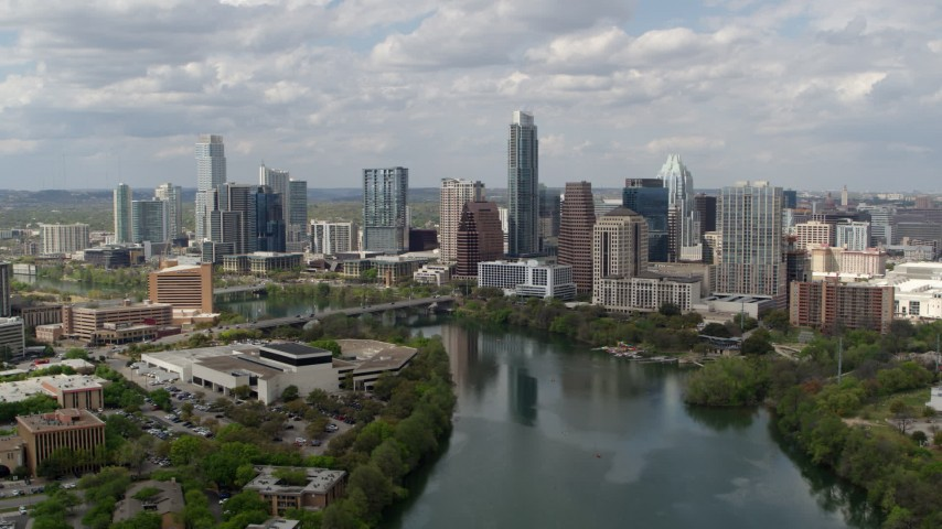 5.7K aerial video slowly fly away from the city skyline while passing over Lady Bird Lake, Downtown Austin, Texas Aerial Stock Footage | DX0002_102_023