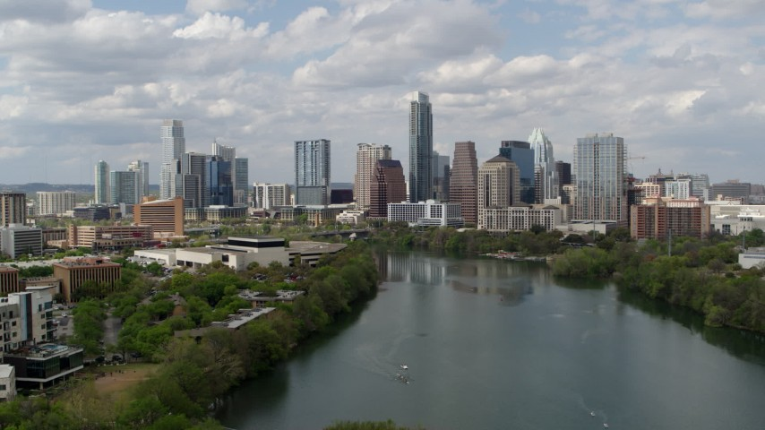 5.7K aerial video descend toward Lady Bird Lake and focus on skyline of Downtown Austin, Texas Aerial Stock Footage | DX0002_102_024