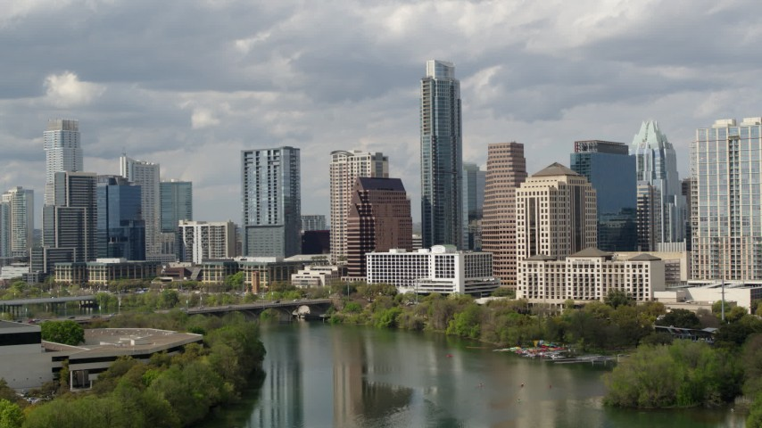 5.7K aerial video fly away from skyscrapers, descend toward Lady Bird Lake in Downtown Austin, Texas Aerial Stock Footage | DX0002_103_002