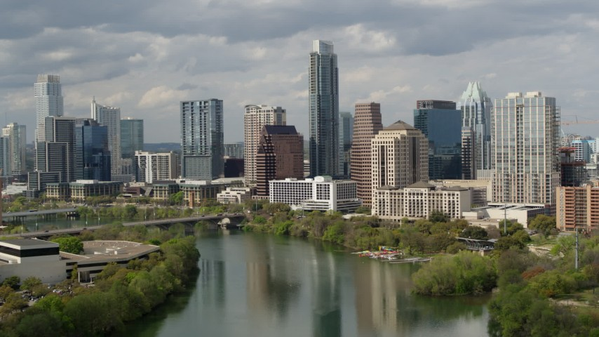 5.7K stock footage aerial video of towering skyscrapers in Downtown Austin, Texas seen while ascending over Lady Bird Lake Aerial Stock Footage | DX0002_103_007