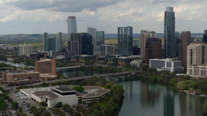 5.7K aerial video fly away from bridge over Lady Bird Lake near waterfront skyscrapers in Downtown Austin, Texas Aerial Stock Footage | DX0002_103_014