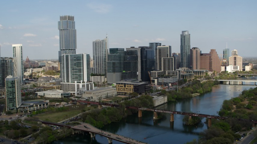 5.7K aerial video flying by skyscrapers and bridges spanning Lady Bird Lake, Downtown Austin, Texas Aerial Stock Footage | DX0002_104_001