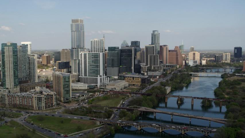 5.7K stock footage aerial video a reverse view of skyscrapers and bridges spanning Lady Bird Lake, Downtown Austin, Texas Aerial Stock Footage | DX0002_104_003