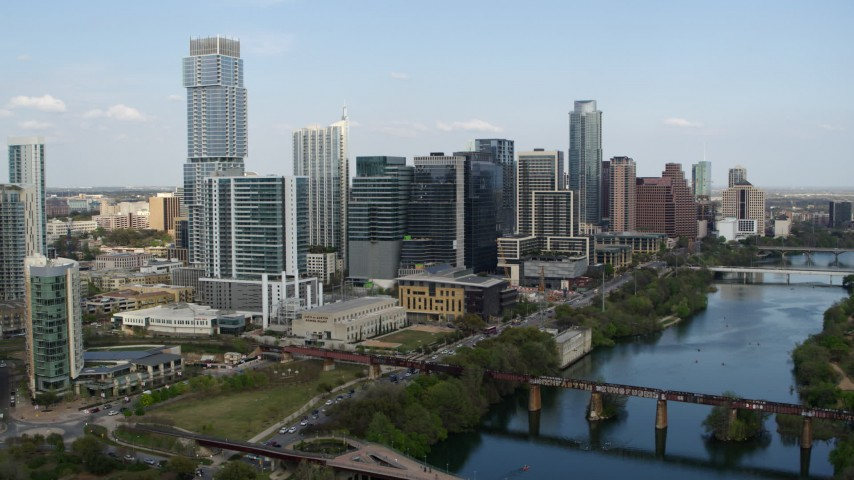 5.7K stock footage aerial video tall skyscrapers seen while flying by bridges over Lady Bird Lake, Downtown Austin, Texas Aerial Stock Footage DX0002_104_006 | Axiom Images