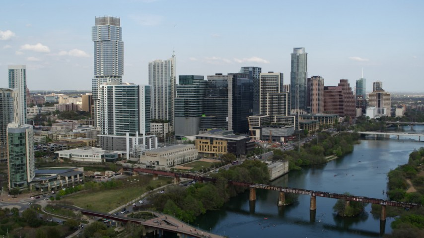 5.7K stock footage aerial video reverse view of tall skyscrapers and bridges over Lady Bird Lake, Downtown Austin, Texas Aerial Stock Footage | DX0002_104_007