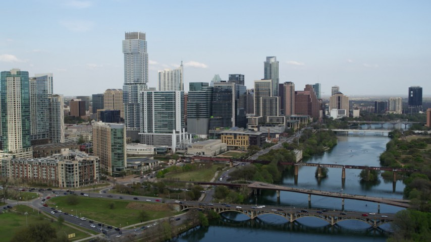 5.7K aerial video fly over Lady Bird Lake to approach towering skyscrapers, Downtown Austin, Texas Aerial Stock Footage | DX0002_104_009