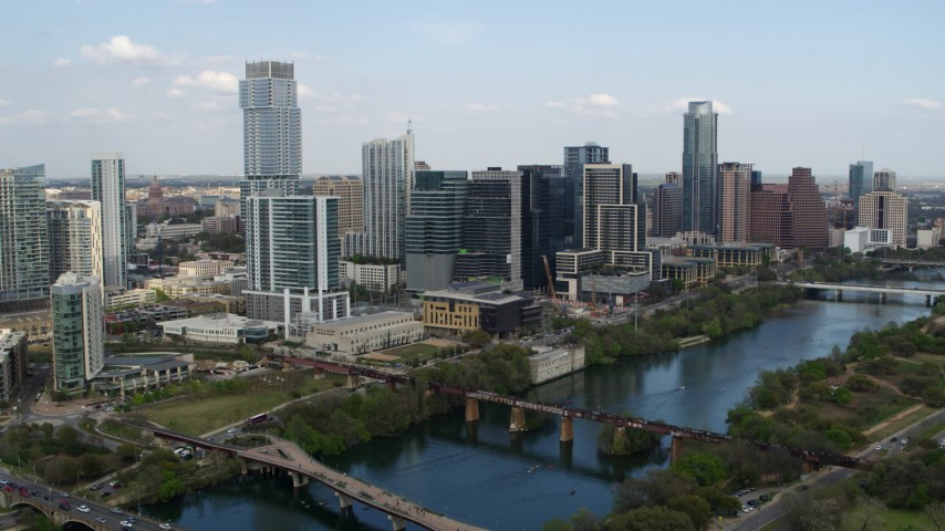 5.7K aerial video approaching towering skyscrapers and bridges over Lady Bird Lake, Downtown Austin, Texas Aerial Stock Footage | DX0002_104_012