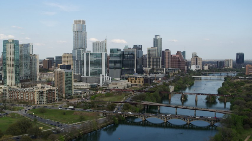 5.7K stock footage aerial video ascend for view of towering skyscrapers and bridges over Lady Bird Lake, Downtown Austin, Texas Aerial Stock Footage | DX0002_104_014