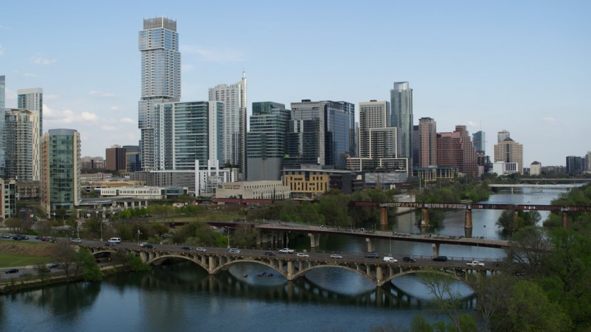 5.7K aerial video descend bridges over Lady Bird Lake with view of skyscrapers, Downtown Austin, Texas Aerial Stock Footage | DX0002_104_016