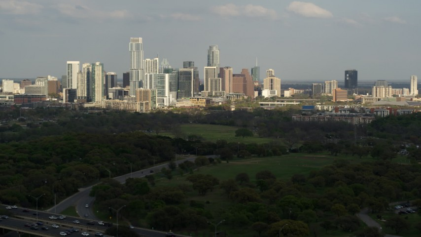 5.7K aerial video of a wide view of city's towering skyline seen from green parks, Downtown Austin, Texas Aerial Stock Footage | DX0002_104_021