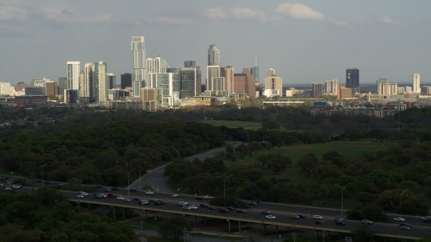 5.7K stock footage aerial video of a wide view of city's towering skyline, descend near freeway, Downtown Austin, Texas Aerial Stock Footage | DX0002_104_022