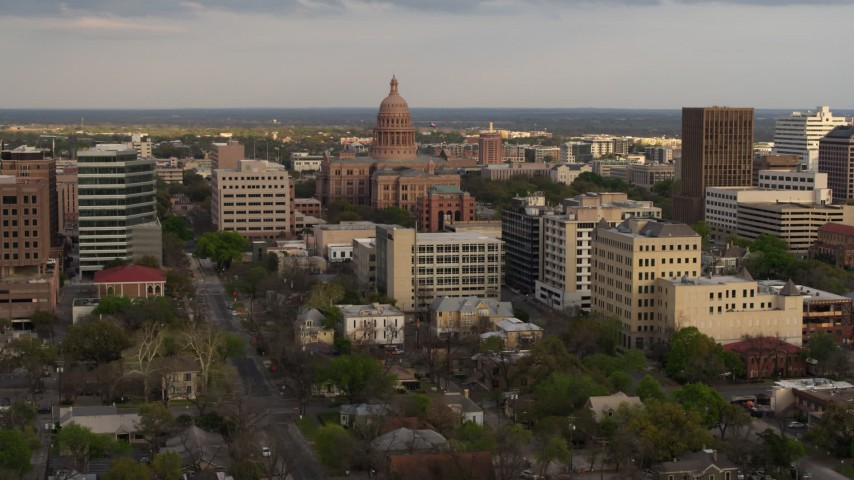 5.7K stock footage aerial video of passing by the Texas State Capitol building at sunset in Downtown Austin, Texas Aerial Stock Footage | DX0002_104_034