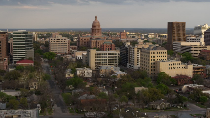 5.7K stock footage aerial video of passing by the Texas State Capitol and office buildings at sunset in Downtown Austin, Texas Aerial Stock Footage | DX0002_104_035