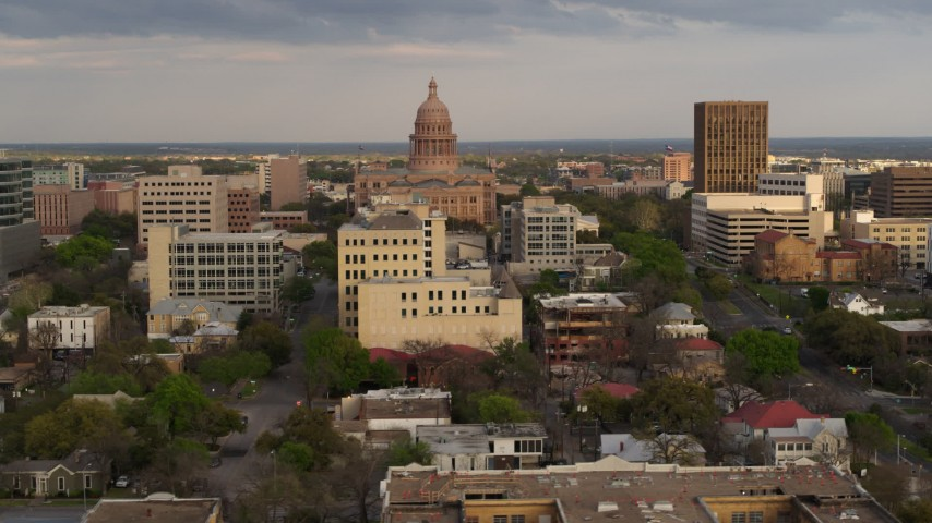 5.7K aerial video of the Texas State Capitol behind office buildings at sunset in Downtown Austin, Texas Aerial Stock Footage | DX0002_104_036