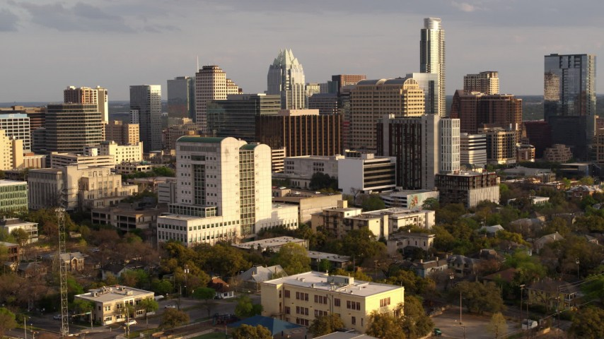 5.7K stock footage aerial video of flying by a courthouse and office buildings near skyscrapers at sunset in Downtown Austin, Texas Aerial Stock Footage | DX0002_104_039