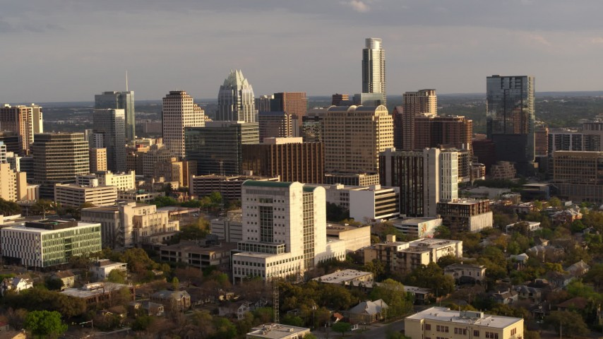 5.7K stock footage aerial video reverse view and flyby of a courthouse and office buildings near skyscrapers at sunset in Downtown Austin, Texas Aerial Stock Footage | DX0002_104_040