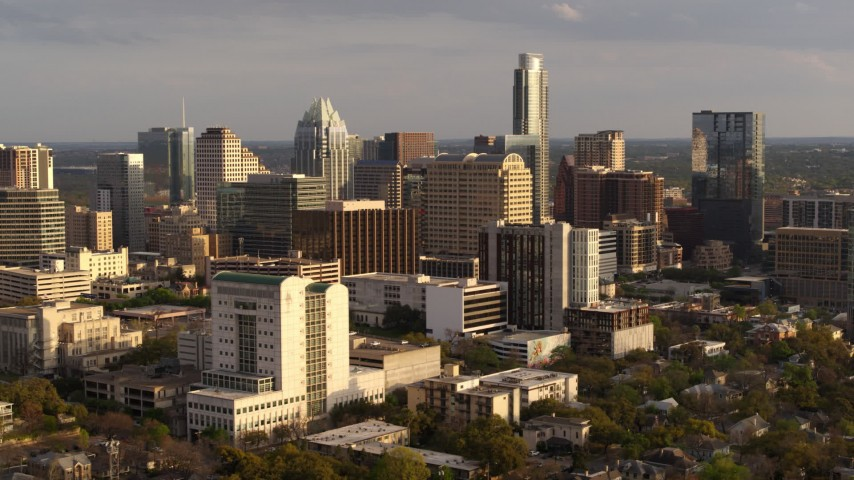 5.7K stock footage aerial video of passing a courthouse and office buildings near skyscrapers at sunset in Downtown Austin, Texas Aerial Stock Footage | DX0002_104_042