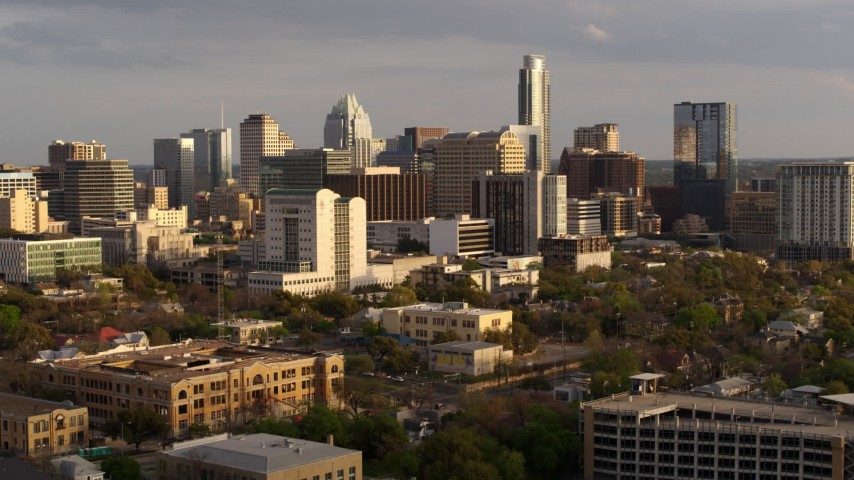 5.7K stock footage aerial video fly away from a courthouse and office buildings near skyscrapers at sunset in Downtown Austin, Texas, and descend Aerial Stock Footage | DX0002_104_043