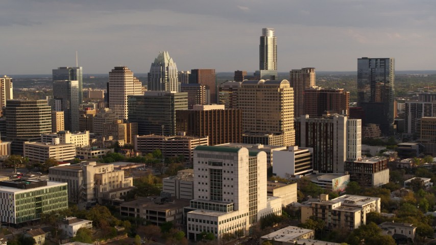 5.7K aerial video passing courthouse near office buildings and skyscrapers at sunset in Downtown Austin, Texas Aerial Stock Footage | DX0002_104_045