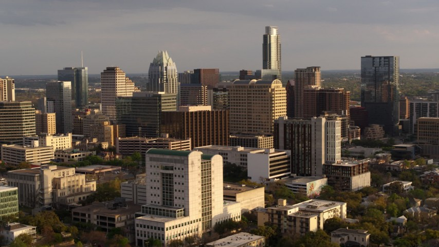 5.7K aerial video flyby courthouse and office buildings near skyscrapers at sunset in Downtown Austin, Texas Aerial Stock Footage | DX0002_104_046