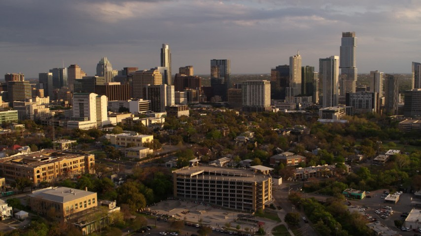 5.7K stock footage aerial video of flying away from skyscrapers and office buildings at sunset in Downtown Austin, Texas Aerial Stock Footage | DX0002_105_003