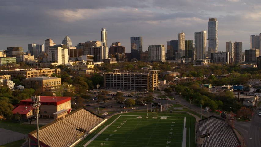 5.7K aerial video a view of skyscrapers and office buildings at sunset in Downtown Austin, Texas, descend by football stadium Aerial Stock Footage | DX0002_105_004