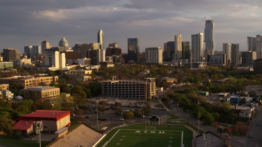 5.7K stock footage aerial video of skyscrapers seen from football field at sunset in Downtown Austin, Texas Aerial Stock Footage | DX0002_105_005