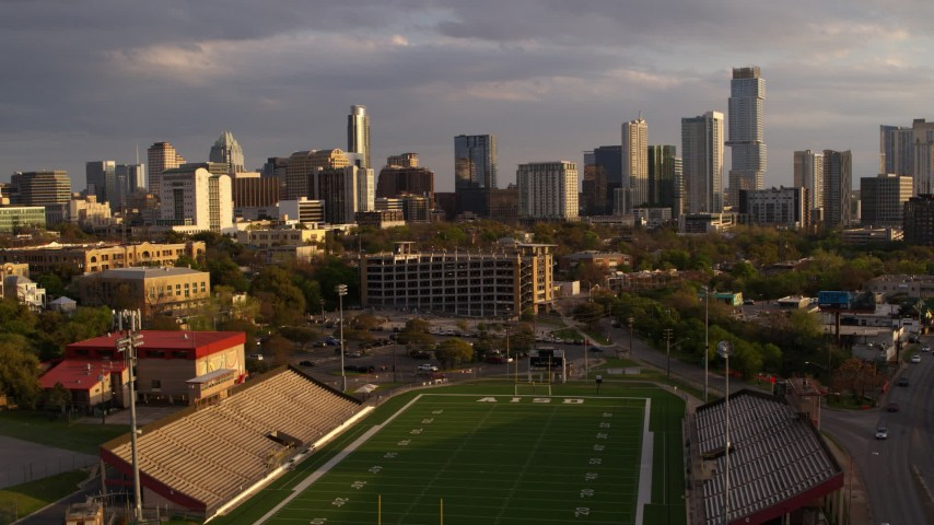 5.7K stock footage aerial video of skyscrapers seen while descending to football field at sunset in Downtown Austin, Texas Aerial Stock Footage | DX0002_105_006