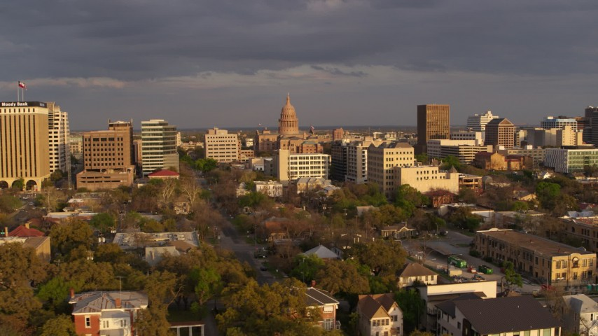 5.7K stock footage aerial video Texas State Capitol dome at the center of office buildings at sunset in Downtown Austin, Texas Aerial Stock Footage | DX0002_105_015