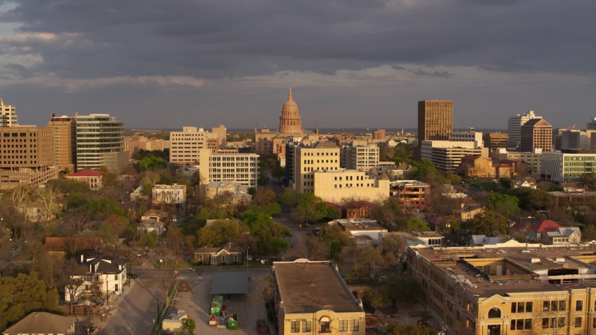 5.7K aerial video Texas State Capitol dome seen while descending near office buildings at sunset in Downtown Austin, Texas Aerial Stock Footage | DX0002_105_016
